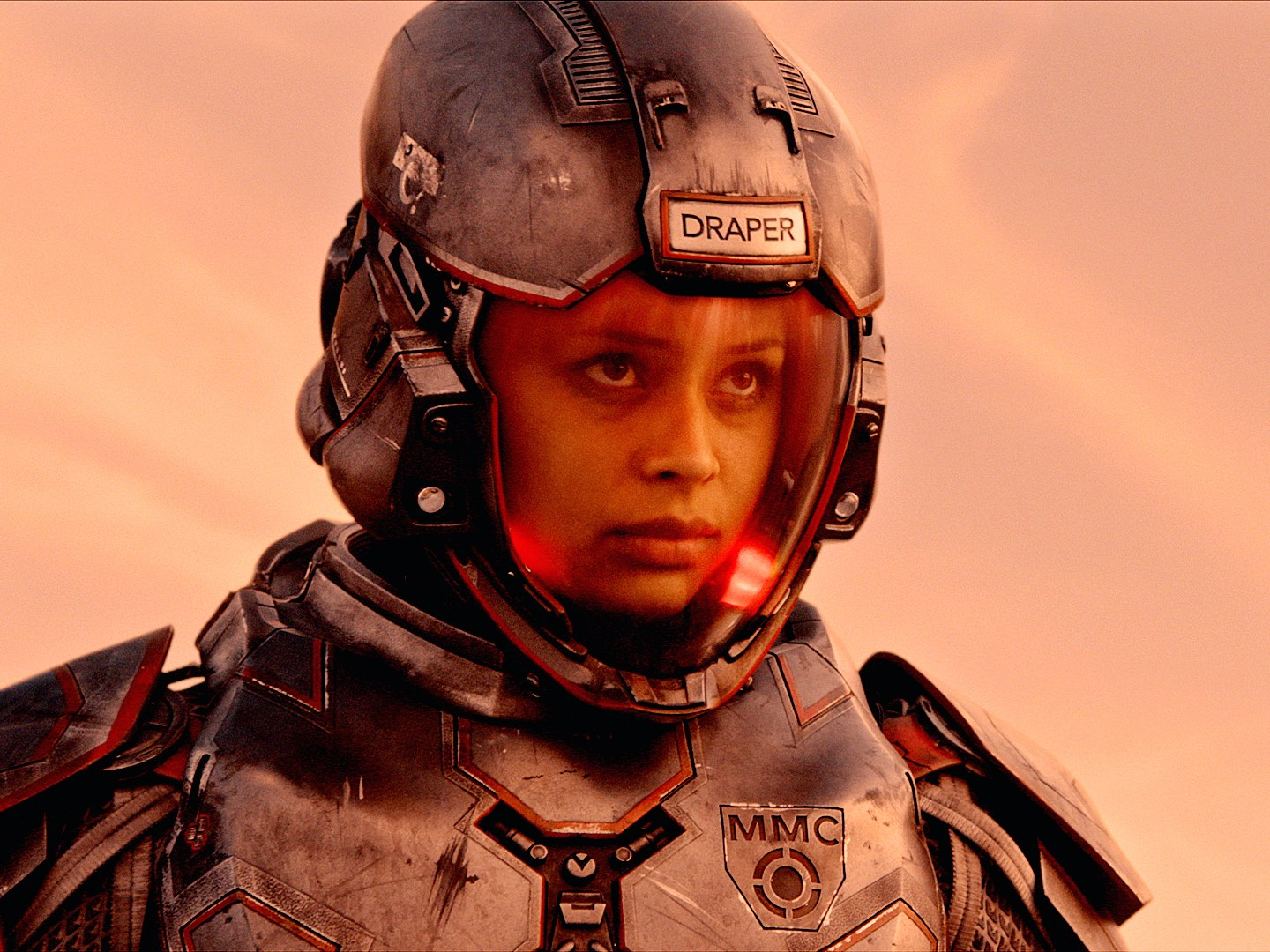 The Image shows the a woman in spacesuit, behind her is a slightly red sky
